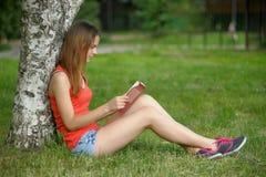 La muchacha en una hierba con el libro Imagenes de archivo