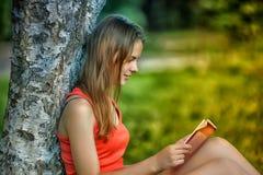 La muchacha en una hierba con el libro Imagen de archivo libre de regalías