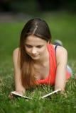 La muchacha en una hierba con el libro Fotos de archivo