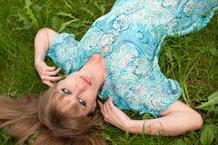 La muchacha en una hierba en una alineada de la turquesa Fotografía de archivo libre de regalías