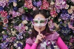 La muchacha en una máscara con las flores Foto de archivo libre de regalías