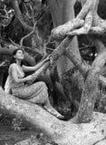 La muchacha en una ramificación de árbol Fotos de archivo libres de regalías
