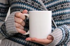La muchacha en una rebeca caliente está sosteniendo la taza blanca en manos Imagen de archivo
