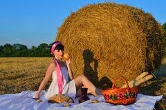 La muchacha en una siega con una cesta de pan y de un jarro de leche Imagen de archivo libre de regalías