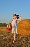 La muchacha en una siega con una cesta de pan y de un jarro de leche Foto de archivo libre de regalías