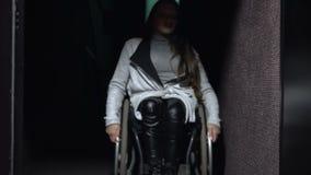 La muchacha en una silla de ruedas que viene en el cine Ocio discapacitado almacen de metraje de vídeo