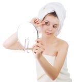 La muchacha en una toalla después de que una ducha, pestañas de las gomas que miran en un espejo Imagen de archivo libre de regalías