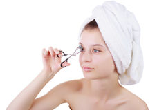 La muchacha en una toalla después de una ducha, con las pinzas que se encrespan de pestañas Foto de archivo