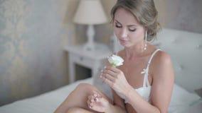 La muchacha en underweare atractivo se sienta en cama con la flor almacen de metraje de vídeo