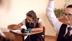 La muchacha en uniforme escribe en la lección metrajes