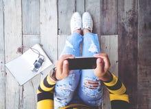 La muchacha en vaqueros con smartphone negro y la cámara retra se sientan en el piso de madera Imagen de archivo libre de regalías