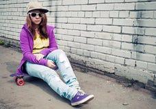 La muchacha en vaqueros y gafas de sol se sienta en el monopatín Imagen de archivo