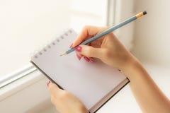 La muchacha en la ventana que sostiene un cuaderno imágenes de archivo libres de regalías