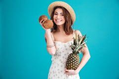 La muchacha en verano viste sostener dos cocos y piñas Imagen de archivo