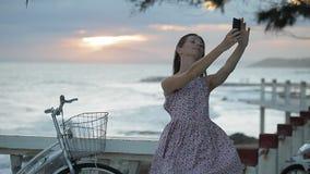 La muchacha en vestido del verano está haciendo el selfie en el terraplén cerca de una playa en la puesta del sol almacen de metraje de vídeo