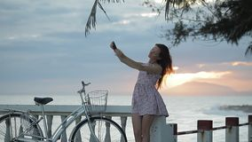 La muchacha en vestido del verano está haciendo el selfie en el terraplén cerca de una playa en la puesta del sol almacen de video