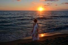 La muchacha en vestido hace una pausa la playa en el ocaso Imágenes de archivo libres de regalías