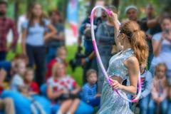 La muchacha en vestido hermoso se realiza con los aros del hula Fotos de archivo