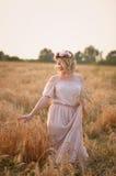 La muchacha en vestido largo rosado y la guirnalda está en campo con centeno Imagen de archivo