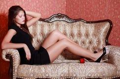 La muchacha en vestido negro corto se sienta en el sofá Imagen de archivo