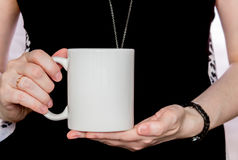 La muchacha en vestido negro está sosteniendo la taza blanca en manos imágenes de archivo libres de regalías