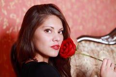 La muchacha en vestido negro sostiene la rosa del rojo Fotografía de archivo libre de regalías