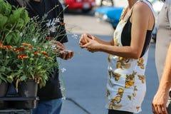 La muchacha en vestido pichi corto y el muchacho con el pelo y la camiseta largos pagan al vendedor por las flores en el mercado  fotos de archivo libres de regalías