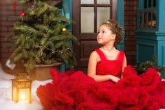 La muchacha en vestido rojo acoge con satisfacción Año Nuevo y la Navidad Foto de archivo