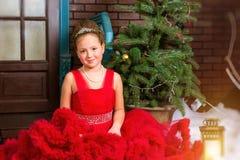 La muchacha en vestido rojo acoge con satisfacción Año Nuevo y la Navidad Fotografía de archivo