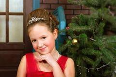 La muchacha en vestido rojo acoge con satisfacción Año Nuevo y la Navidad Imagenes de archivo