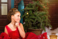 La muchacha en vestido rojo acoge con satisfacción Año Nuevo y la Navidad Imagen de archivo