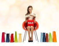 La muchacha en vestido rojo con los zapatos, el bolso y la venta firman Imagen de archivo libre de regalías