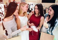 La muchacha en vestido rojo está sosteniendo un zapato blanco y está mirando a sus amigos La han rodeado Todos están sonriendo imágenes de archivo libres de regalías