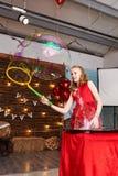 La muchacha en vestido rojo hace burbujas de jabón grandes Imágenes de archivo libres de regalías