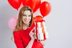 La muchacha en vestido rojo sostiene las cajas con los regalos imagen de archivo