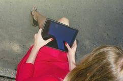 La muchacha en vestido rojo utiliza una tableta en la calle Visión desde arriba Foto de archivo