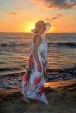La muchacha en vestido y cuidado hace una pausa la playa en el ocaso Fotos de archivo libres de regalías