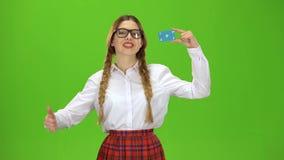 La muchacha en vidrios aumenta una tarjeta y muestra los pulgares para arriba que sonríe Pantalla verde metrajes