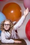La muchacha en vidrios con la mano aumentada quiere pedir Imágenes de archivo libres de regalías