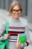 La muchacha en vidrios con los cuadernos y backpacker se coloca foto de archivo libre de regalías