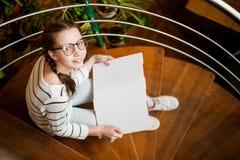 La muchacha en vidrios con un libro en sus manos fotografía de archivo libre de regalías