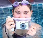 La muchacha en vidrios de agua se cierra con la cámara subacuática Imagen de archivo libre de regalías