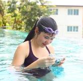 La muchacha en vidrios de agua se cierra con la cámara subacuática Fotos de archivo libres de regalías