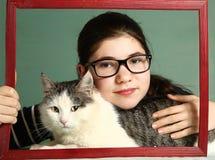 La muchacha en vidrios de la miopía abraza el gato siberiano grande Foto de archivo libre de regalías