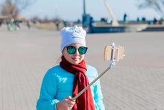 La muchacha en vidrios del espejo hace una foto del uno mismo del teléfono Foto de archivo libre de regalías