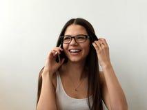 La muchacha en vidrios está hablando feliz en el teléfono Risa Fondo blanco Foto de archivo