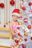 La muchacha en vidrios redondos y un sombrero rojo de la Navidad cuelga bolas en un árbol de navidad nevoso de los Años Nuevos Foto de archivo libre de regalías