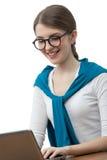 La muchacha en vidrios trabaja en el ordenador fotografía de archivo