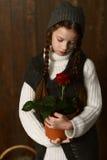 La muchacha en vintage viste con el sombrero hecho punto, coletas, mirando las flores Imagen de archivo libre de regalías