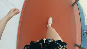 La muchacha en zapatillas de deporte va a encontrar a un individuo en zapatillas de deporte Muchacha en pantalones cortos almacen de video